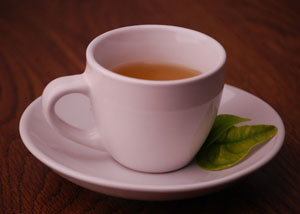 Cup of tea on white saucer with green tea leaves on the side
